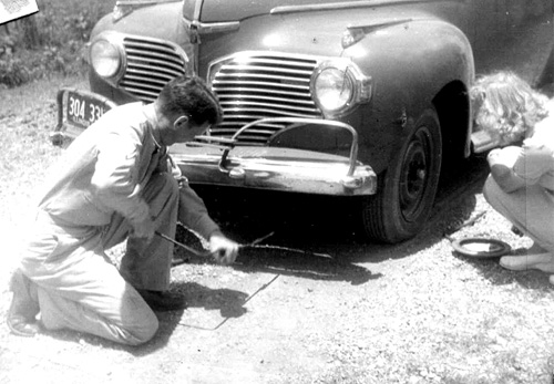 T/5 Soper fixes a flat along a Mississippi Highway-1944